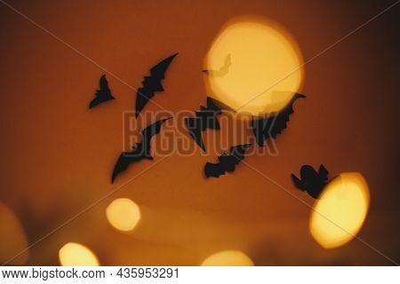 Happy Halloween. Bats Flying On Dark Orange Background With Magical Lights Bokeh. Atmospheric Hallow