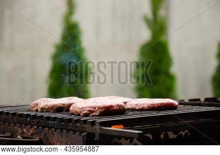 Raw Meatballs For Burgers Are Fried On Grill On Background Of Trees. Meat Is Roasting On Bbq Grill O