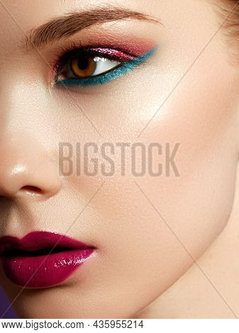 Cosmetics Products. Close Up Of Cheerful Young Woman With Colorful Makeup. Beauty Portrait Of Female