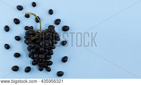 Fresh Ripe Black Grapes On A Blue Background With Copy Space