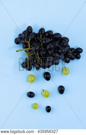 Fresh Ripe Black Grapes And Green Grapes On A Blue Background