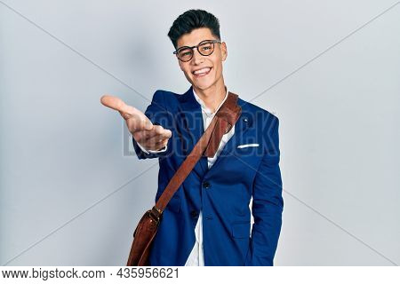 Young hispanic man wearing business clothes smiling friendly offering handshake as greeting and welcoming. successful business.