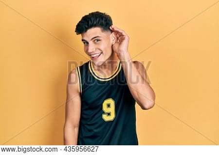 Young hispanic man wearing basketball uniform smiling with hand over ear listening an hearing to rumor or gossip. deafness concept.
