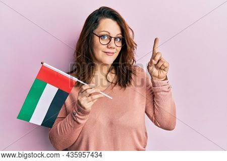 Young caucasian woman holding united arab emirates flag smiling with an idea or question pointing finger with happy face, number one