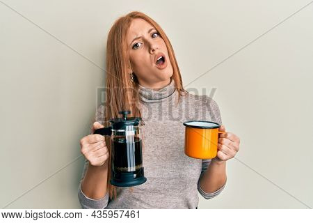 Young irish woman drinking italian coffee in shock face, looking skeptical and sarcastic, surprised with open mouth