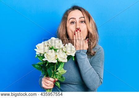 Middle age caucasian woman holding flowers covering mouth with hand, shocked and afraid for mistake. surprised expression