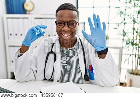 Young african doctor man holding syringe at the hospital waiving saying hello happy and smiling, friendly welcome gesture