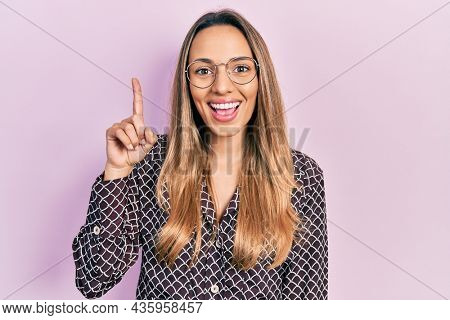 Beautiful hispanic woman wearing casual clothes and glasses pointing finger up with successful idea. exited and happy. number one.
