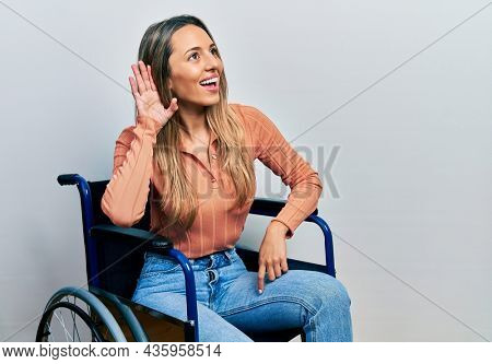 Beautiful hispanic woman sitting on wheelchair smiling with hand over ear listening and hearing to rumor or gossip. deafness concept.