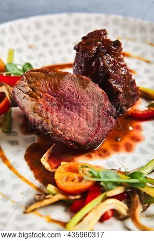 Roasted Beef fillet with vegetables. Roasted Mignon steak with paprika and celery. Beef tenderloin with garnish. Beef steak medium rare doneness. Delicious meat menu. Dish concept with angus beef