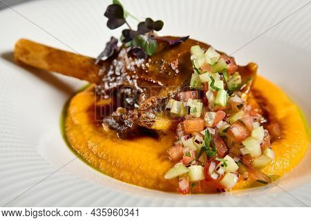 Slow roast leg of lamb with pumpkin puree and vegetables salsa. Roasted lamb with vegetables on gray stone table. Composition with meat dish on stone background. Meat menu ideas