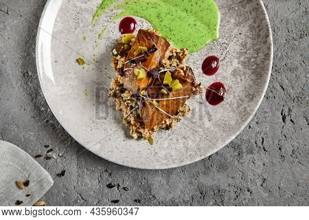 Roasted beef tongue with green buckwheat and green sauce. Main course with beef tongue and garnish on gray stone table. Aesthetic composition with meat dish and textile. Beef in restaurant menu