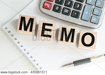 Memo Word On Wooden Cubes On A Table On A White Notepad Next To A Calculator