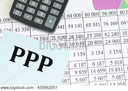Ppp Text On A Blue Card On The Table Next To A Calculator And Paper With Numbers And Diagrams