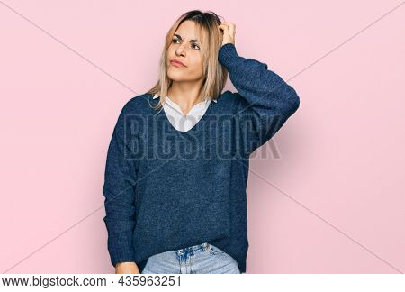 Young caucasian woman wearing casual clothes confuse and wondering about question. uncertain with doubt, thinking with hand on head. pensive concept.