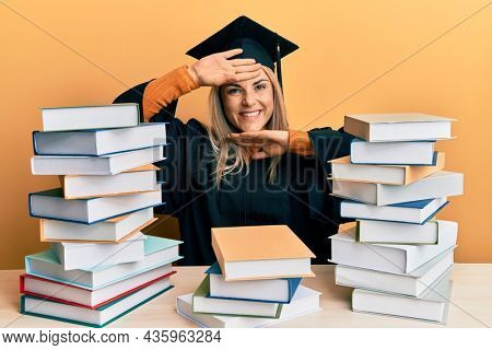 Young caucasian woman wearing graduation ceremony robe sitting on the table smiling cheerful playing peek a boo with hands showing face. surprised and exited