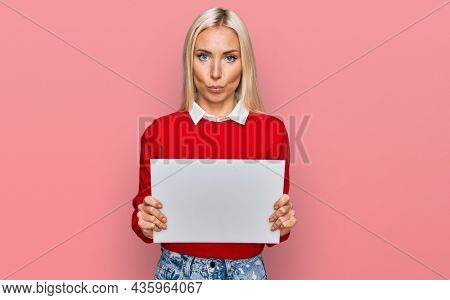 Young blonde woman holding blank empty banner thinking attitude and sober expression looking self confident