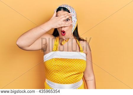 Young hispanic woman wearing pin up style peeking in shock covering face and eyes with hand, looking through fingers afraid