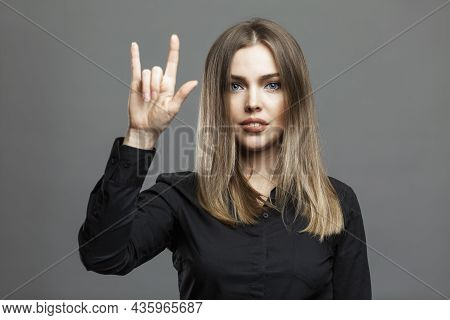 Young Woman Shows Sign Of Goat With Her Hand. Beautiful Blonde In A Black Shirt. Masonic Symbol, Wor