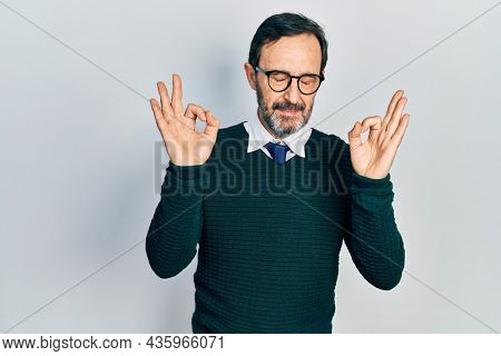 Middle age hispanic man wearing casual clothes and glasses relax and smiling with eyes closed doing meditation gesture with fingers. yoga concept.