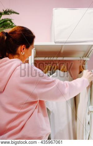 A Young Woman Organizes Clothes In A Closet. Viewing Things In The Closet And Choosing What To Wear.