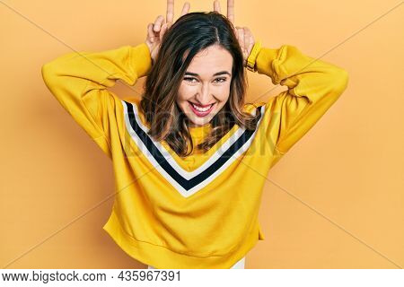 Young hispanic girl wearing casual clothes posing funny and crazy with fingers on head as bunny ears, smiling cheerful