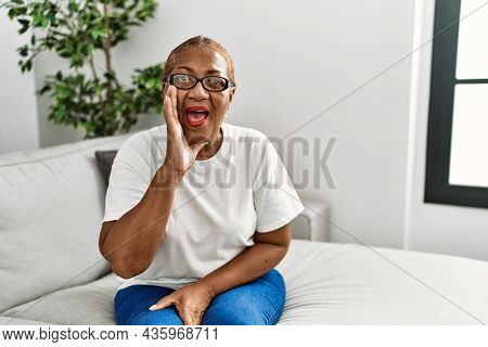 Mature hispanic woman sitting on the sofa at home shouting and screaming loud to side with hand on mouth. communication concept.