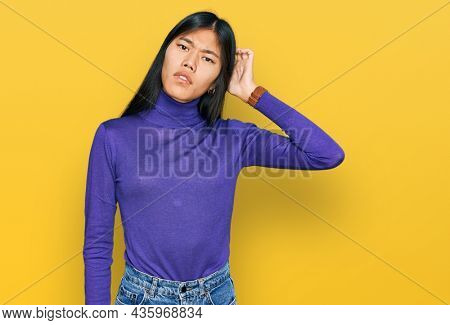 Beautiful young asian woman wearing casual clothes confuse and wondering about question. uncertain with doubt, thinking with hand on head. pensive concept.