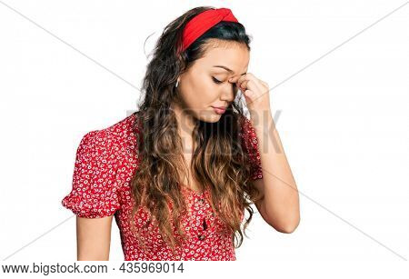 Young hispanic girl wearing casual clothes tired rubbing nose and eyes feeling fatigue and headache. stress and frustration concept.