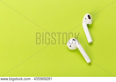 Modern White Wireless Earphones With Charging Case On Green Background