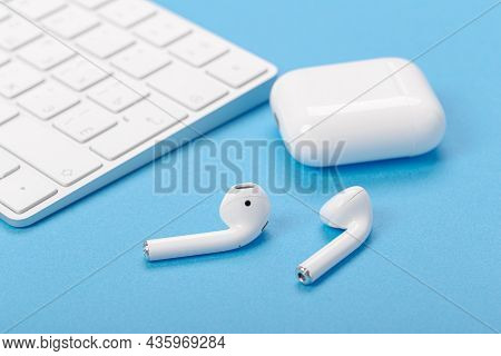 Wireless Bluetooth Earphones With Charging Case On A Blue Background. The Concept Of Modern Technolo