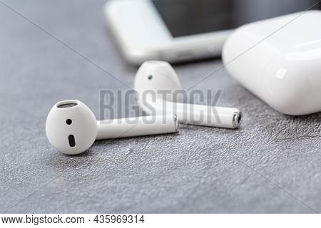 Modern Wireless Bluetooth Headphones With Charging Case Near Mobile Phone On Gray Table
