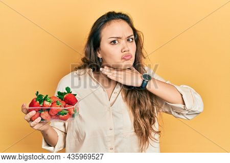 Young hispanic girl holding strawberries cutting throat with hand as knife, threaten aggression with furious violence