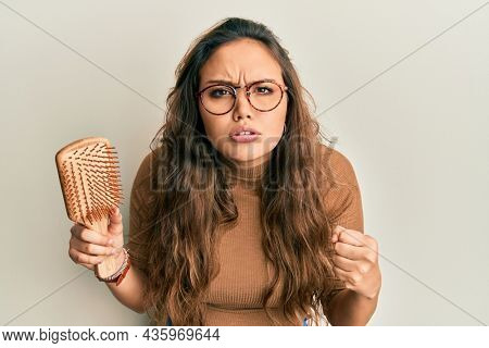 Young hispanic girl holding hair comb annoyed and frustrated shouting with anger, yelling crazy with anger and hand raised