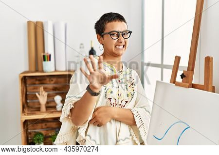 Young hispanic woman with short hair at art studio disgusted expression, displeased and fearful doing disgust face because aversion reaction. with hands raised