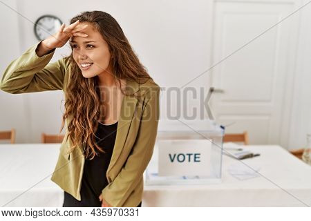 Beautiful hispanic woman standing at political campaign room very happy and smiling looking far away with hand over head. searching concept.