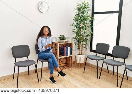 Young latin woman listening to music sitting on chair at waiting room