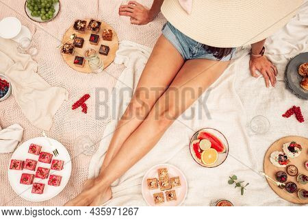 Top View Image Of Woman Sitting Around Cakes, Food, Fruits And Wine On Blanket - Picnic Style. Femal