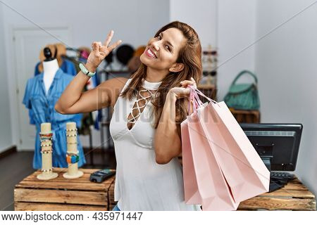 Middle age hispanic woman holding shopping bags at retail shop smiling looking to the camera showing fingers doing victory sign. number two.