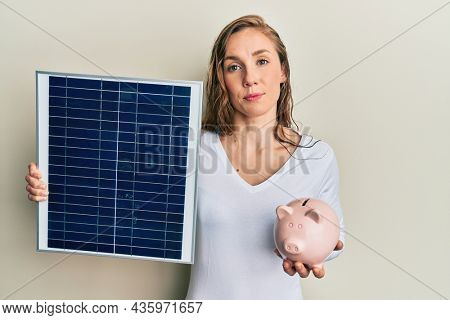 Young blonde woman holding photovoltaic solar panel and piggy bank relaxed with serious expression on face. simple and natural looking at the camera.