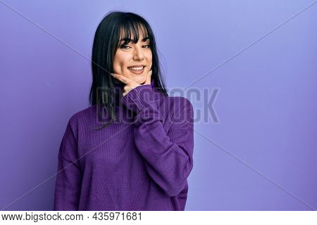 Young brunette woman with bangs wearing turtleneck sweater looking confident at the camera smiling with crossed arms and hand raised on chin. thinking positive.