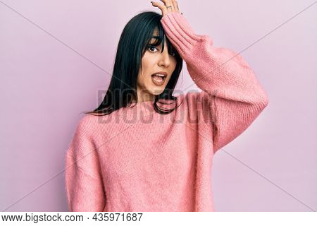 Young brunette woman with bangs wearing casual winter sweater surprised with hand on head for mistake, remember error. forgot, bad memory concept.