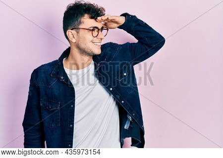 Young hispanic man wearing casual clothes and glasses very happy and smiling looking far away with hand over head. searching concept.