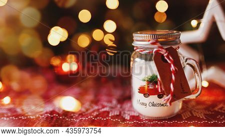 Festive Christmas Candle In Form Of Glass Cup Or Mug And Other Decorations, Blurred Background With