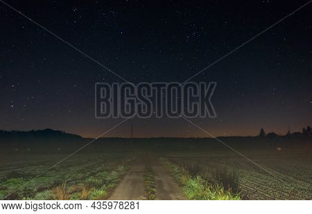 Unpaved Road Through The Plain Covered With Farmland And Meadows. It Is Night, The Road Is Illuminat