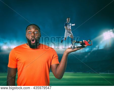 Soccer Players Compete For The Ball On The Hand Of An Astonished Fan