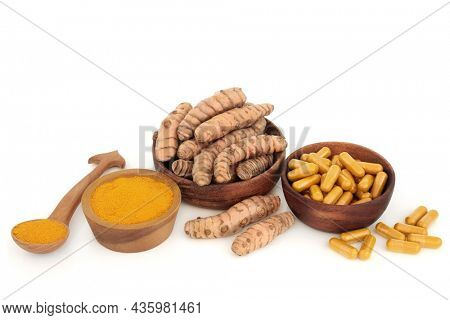Turmeric root spice with powder and dietary supplement capsules. Food seasoning and natural herbal medicine. Is anti inflammatory, an antioxidant with many health benefits. On white.