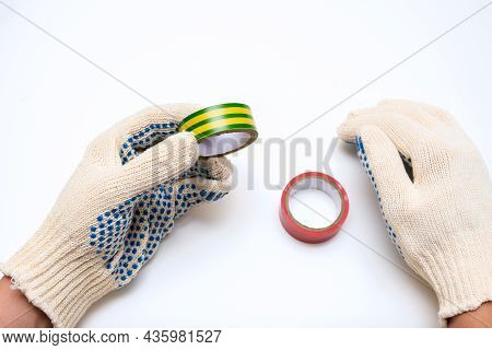 Hands Of A Worker, Electrician In Protective Gloves Holding Rolls Of Electrical Isonation Duct Tape,