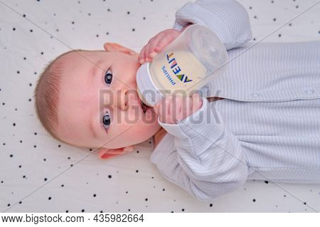 Happy Baby Is Smiling On Her Own Holding A Bottle Philips Avent In Her Hands. Three Month Old Child