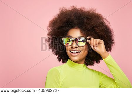 Beauty Portrait Of African Girl In Colored Holographic Sunglasses. Beautiful Woman On Pink Backgroun